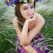 Beautiful young woman with flower wreath in the grass of feather — Stock Photo