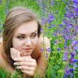 Stock Photo: Beautiful young womin violet flowers outdoors