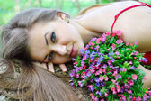 Beautiful young woman with the bouquet of spring flowers — ストック写真