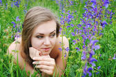 Beautiful young woman in violet flowers outdoors — Стоковое фото