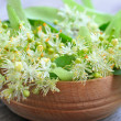 Flowers of linden tree in wooden bowl — Stock Photo