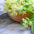 Flowers of linden tree in wooden bowl — Stock Photo #28139071