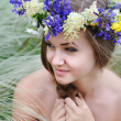 Beautiful young woman with flower wreath in the grass of feather-grass outdoors — Stock Photo