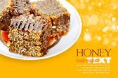 Les nids d'abeille sucrés avec du miel sur la plaque sur un fond jaune — Photo