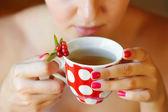 Cowberry (Vaccinium vitis-idaea) tea in woman hands — Stock Photo