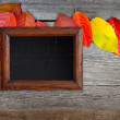 Old wooden frame and autumn leaves over old wooden background — Stock Photo