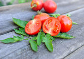 Tomatoes are with leaves on an old wooden table — Stock Photo