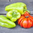 Fresh tomatoes (sort Beauty Lottringa) and sweet green pepper on an old wooden table — Stock Photo