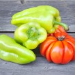 Fresh tomatoes (sort Beauty Lottringa) and sweet green pepper on an old wooden table — Stock Photo #31555037