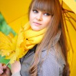 Beautiful young woman with a yellow umbrella — Stock Photo