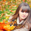 Portrait of beautiful young woman with autumn leaves — Stock Photo #33859231
