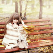 Beautiful young woman sits on a bench in an autumn park — Stock Photo