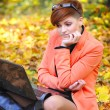 Cute woman with laptop in the autumn park — Стоковая фотография