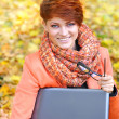 Cute woman with laptop in the autumn park — Stock Photo