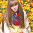 Beautiful girl with notebook on a background autumn leaves — Lizenzfreies Foto