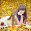 Beautiful girl with notebook on a background autumn leaves — Stockfoto