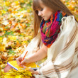 Beautiful girl with notebook on a background autumn leaves — Foto Stock