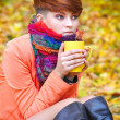 Young beautiful woman that holds the cup of tea in hands on a background autumn leaves — Stock Photo