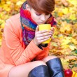 Young beautiful woman that drinks tea on a background autumn leaves — Stock Photo