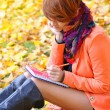 Red-haired student girl with notebook on a background autumn leaves — Stock Photo