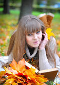 Beautiful girl with book in the autumn park — Stockfoto