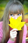 Young woman with autumn leaf in hand — Stock Photo