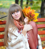 Beautiful young woman sits on a bench with autumn leaves — Stockfoto