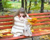 Beautiful young woman sits on a bench with autumn leaves — Stock Photo
