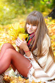 Young beautiful woman that holds the cup of tea in hands on a background autumn leaves — Foto de Stock