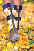 Woman walking on a street with autumn leaves — Stock Photo