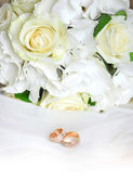 Gold wedding rings on a white veil and wedding roses bouquet — Stock Photo