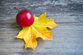 Red apple are with autumn leaf over old wooden background. With — Stock Photo