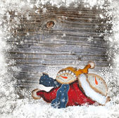 Snow man on a wooden snowbound background — Stock Photo