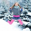 Happy young beautiful woman jumping in winter park — Photo