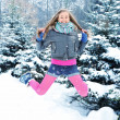 Happy young beautiful woman jumping in winter park — Foto Stock