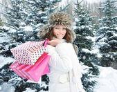 Vackra glad flicka med påsar i en winter park — Stockfoto