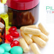 Color pills and medical bottle (with sample text) — Stock Photo