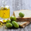 Green olives with pieces of bread and a bottle of oil on wooden table — Stock Photo