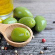 Green olives in a wooden spoon with oil and color peppers on a wooden background — Stock Photo