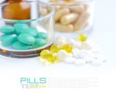 Heap of colorful pills and glass on a white background — Stock Photo