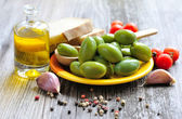 Green olives with spices, bread and oil on a wooden background — Photo