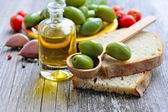 Green olives on a wooden spoon on a slice of bread — Stock Photo