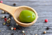 Green olives in a wooden spoon with color peppers on a wooden background — Stock Photo