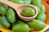 Green olives in a wooden spoon — Stock Photo