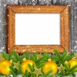 Old frame with gold christmas decoration baubles and pine on a snowbound wooden background — Stock Photo #36504527