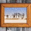 Frame with winter landscape on a wooden background — Stock Photo