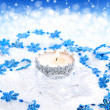 Christmas candle with blue snowflakes on a festive background — Stock Photo