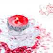 Christmas candle on red spangles asterisks — Stock Photo
