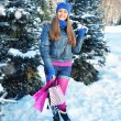 Beautiful happy girl with shopping bags in a winter park — Stock Photo