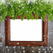 Old frame with snowbound branches of spruce on wooden background — Stock Photo